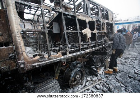KYIV, UKRAINE - JAN 21: Young men look at the burned out military auto on the barricades of occupying snow city during anti-government protest Euromaidan on January 21, 2014, in Kiev, Ukraine - stock photo