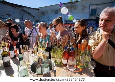 KYIV, UKRAINE - JUNE 6, 2015: Crowd of people tasting red and white wine in outdoor bar during Kiev Food & Wine Festival on June 20, 2014. Ukrainian capital, Kiev has population near 2,900,200  - stock photo