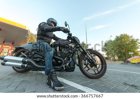 Kyiv, Ukraine - June 17th, 2015: A man in black on a black Harley Davidson - stock photo