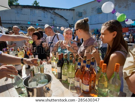 KYIV, UKRAINE - JUNE 6, 2015: Women tasting red and white wine in outdoor bar of summer Kiev Food & Wine Festival on June 20, 2014. Kiev is 8th largest city in Europe with populat. of 2,900,000 - stock photo