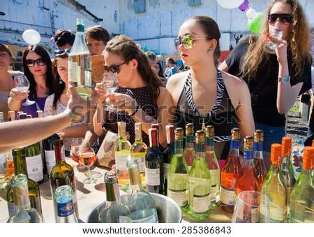 KYIV, UKRAINE - JUNE 6, 2015: Young women in glasses buying wine from bartender at outdoor bar during Kiev Food & Wine Festival on June 20, 2014. Ukrainian capital, Kiev has population near 2,900,200  - stock photo