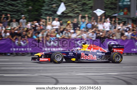 KYIV, UKRAINE - MAY 19, 2012: Daniel Ricciardo of Red Bull Racing Team drives RB7 racing car during Red Bull Champions Parade on the streets of Kyiv city - stock photo