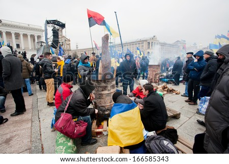 KYIV, UKRAINE - NOV 28: Young people with the flags sitting by the barrel with fire on the cold occupying street during two weeks of anti-government protest on November 28, 2013, in Kiev, Ukraine. - stock photo