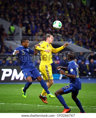 KYIV, UKRAINE - NOVEMBER 15, 2013: Roman Zozulya of Ukraine (C) fights for a ball with Eric Abidal (L) and Patrice Evra (R) of France during their FIFA World Cup 2014 play-off game - stock photo