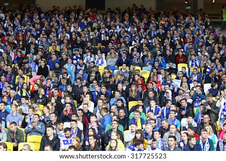 KYIV, UKRAINE - SEPTEMBER 16, 2015: People seat on the tribunes of NSC Olimpiyskyi stadium during UEFA Champions League game between FC Dynamo Kyiv and FC Porto - stock photo
