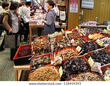 KYOTO, JAPAN - APRIL 19: Shoppers walk along Nishiki market on April 19, 2012 in Kyoto, Japan. According to Tripadvisor, it is currently the top shopping place in Kyoto. - stock photo