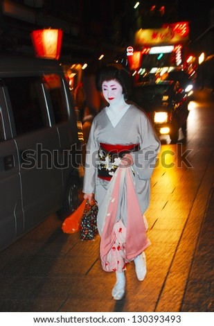 KYOTO,JAPAN-APRIL 4:Unidentified woman walking by an old street at night on April 4,2010 in Gion,Kyoto,Japan.Geisha are professional entertainers who attend guests,banquets and other occasions. - stock photo