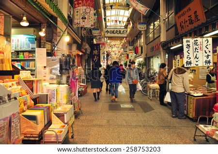 KYOTO, JAPAN - MARCH 1, 2013: Shoppers walk along Demachi Masugata Archade. This small arcade mall located near Nishiki market, one of the the top shopping places in Kyoto. - stock photo