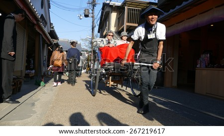 Kyoto, Japan - March 28: Tourist riding a rickshaw in Arashiyama, a tourist district in Kyoto on March 28, 2015. Rickshaw is a popular mode of transportation in Japan in the 19th century. - stock photo