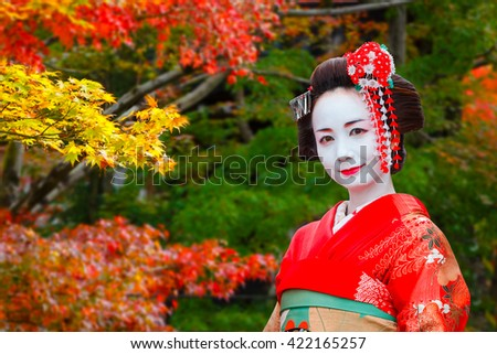 """KYOTO, JAPAN - NOVEMBER 22 2015: An unidentified """"Maiko"""" girl or apprentice Geisha is in a Japanese garden in autumn - stock photo"""