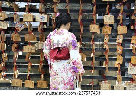 KYOTO, JAPAN-NOVEMBER 4, 2014; Geisha in front of prayer tablets at Rokuharamitsuji Temple. People write their wish on a wooden tablet (ema) November 4, 2014 Kyoto, Japan - stock photo