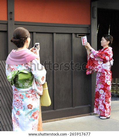 KYOTO,JAPAN-NOVEMBER 3, 2014;Geisha taking a photo of an other geisha that puts a letter through the mail. November 3, 2014 Kyoto, Japan - stock photo