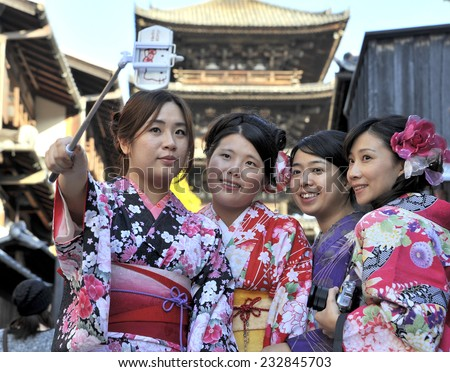 KYOTO,JAPAN - NOVEMBER 4: Geisha women in traditional dress making a selfie with a telephone in front of the Yasaka-no-To Pagoda. November 4, 2014 Kyoto, Japan.  - stock photo