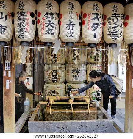 KYOTO,JAPAN-NOVEMBER 3, 2014; People collecting water at Nishiki Tenmangu Shrine.The shrine is located in the heart of Nishiki food market street.November 3, 2014 Kyoto, Japan - stock photo