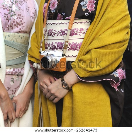 KYOTO; JAPAN - NOVEMBER 3, 2014: Two Geishas wearing kimonos; one of them with a small digital camera. The kimono is a traditional Japanese dress. . November 3; 2014 Kyoto; Japan - stock photo