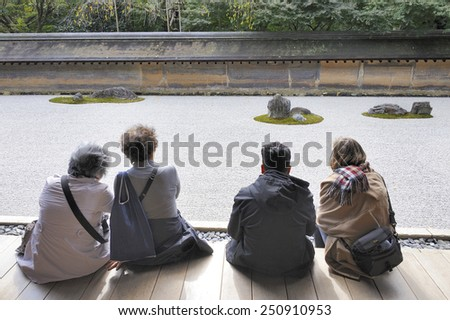KYOTO, JAPAN-NOVEMBER 10, 2014;Visitors watching the Hojo Zen Rock Garden at the Ryoanji Temple.This is an UNESCO world heritage site. November 10, 2014 Kyoto, Japan - stock photo