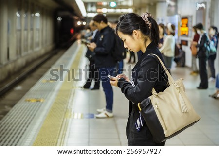 KYOTO, JAPAN - OCTOBER 23: People on a platform in Kyoto, Japan on October 23, 2014. Unidentified Japanese female uses her device while waits for a train on a plateform - stock photo