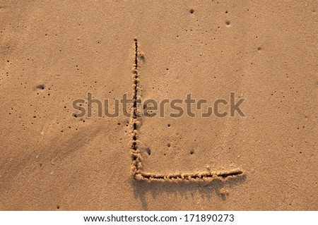 L text written in the sandy on the beach - stock photo