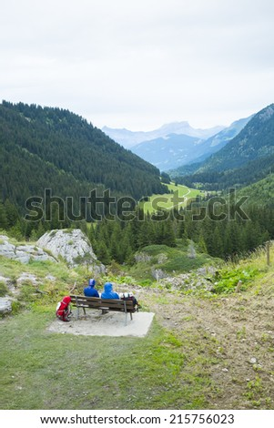 LA BALME, FRANCE - AUGUST 25: Hikers doing the Mont Blanc tour resting on bench in La Balme overlooking La Rollaz. The tour crosses France, Italy and Switzerland. August 25, 2014 in La Balme. - stock photo