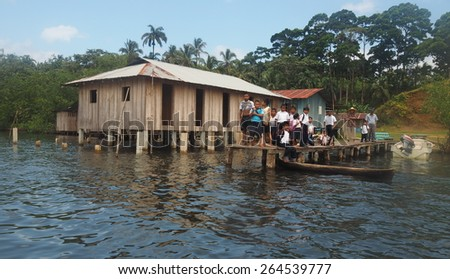 La Ensenda, Ngobe Bugle/Panama - March 5: School children and adult community members gather on a dock watching departing tourists.  Tourism in remote locations is being developed by government - stock photo