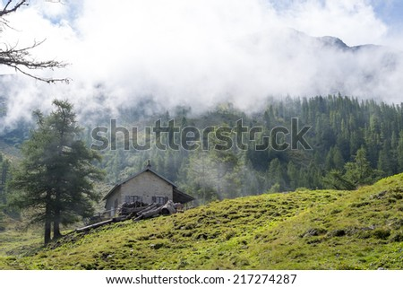 LA GIETE, SWITZERLAND - AUGUST 31: Refuge with misty forest on mountain in the background. The refuge is on a stage of the popular Mont Blanc tour. August 31, 2014 in La Giete. - stock photo