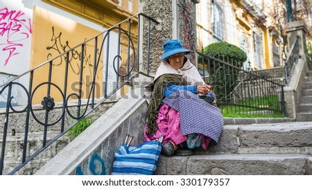 La Paz, Bolivia - Circa March 2015 - Old woman sitting on a street stairs in La Paz - stock photo