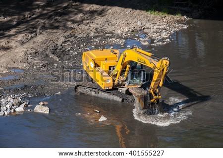 LA POLA DE GORDON - JULY 14, 2014: Backhoe working in the River Bernesga, in La Pola de Gordon, Leon Province, Spain, on July 14, 2014. - stock photo