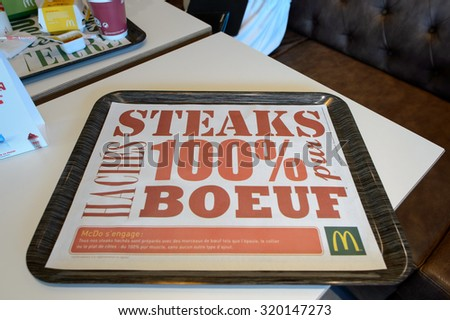 LA VILLE-AUX-DAMES, FRANCE - AUGUST 12, 2015: tray with McDonald's ad. McDonald's is the world's largest chain of hamburger fast food restaurants, founded in the United States. - stock photo