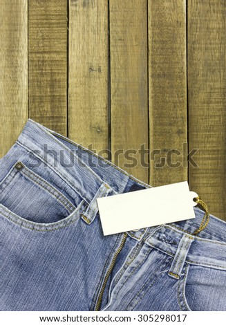 label tag and jeans on wood background. - stock photo