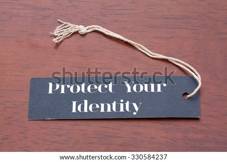 Label tag with protect your identity word on wood background - stock photo