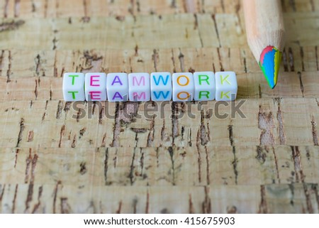 "Label word ""TEAMWORK"" written on plastic blocks, wood background with copyspace. - stock photo"