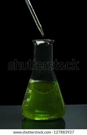 Laboratory beaker filled with green color liquid substances and laboratory pipette. Dark background - stock photo