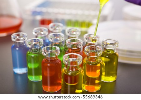 laboratory colorful test tubes, pipette with yellow fluid over one of the bottles, science, experiment - stock photo