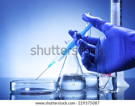Laboratory equipment, syringe in hand glass bowl - stock photo