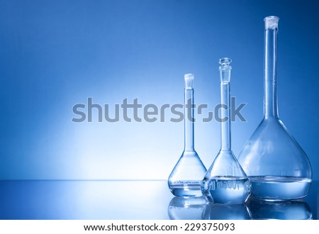 Laboratory equipment, three glass flask on blue background - stock photo