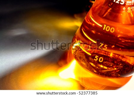Laboratory glass conical Erlenmeyer flask filled with liquid for an experiment in a science research lab - stock photo