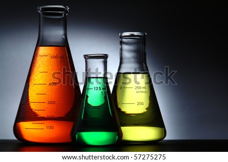 Laboratory glass conical Erlenmeyer flasks filled with red chemical with green and yellow liquid solution for an experiment in a science research lab - stock photo