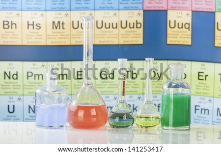 Laboratory glassware with chemical chart background - stock photo