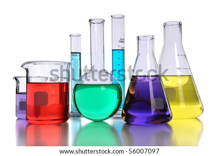 Laboratory glassware with various colored liquids with reflection on table - stock photo