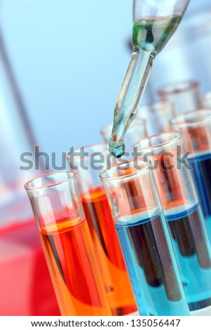 Laboratory pipette with drop of color liquid over glass test tubes, close up - stock photo