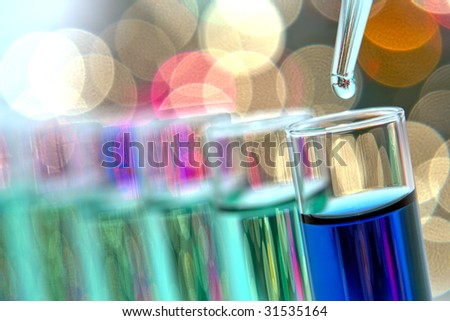 Laboratory pipette with drop of green liquid over glass test tubes filled with blue chemical solution for an experiment in a science research lab - stock photo