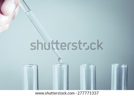 Laboratory pipette with drop of liquid over glass test tubes - stock photo