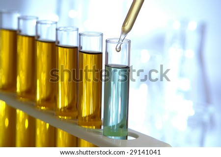 Laboratory pipette with drop of yellow liquid over glass test tubes filled with blue chemical solution for an experiment in a science research lab - stock photo