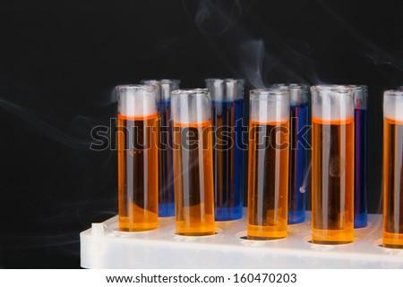 Laboratory test tubes on black background - stock photo