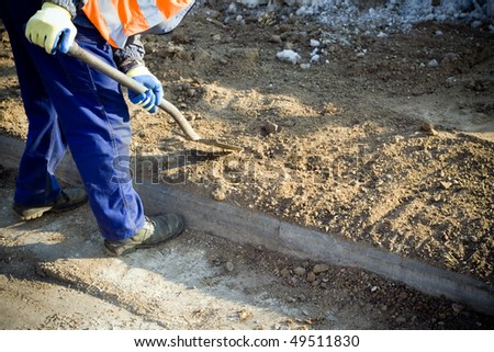 Laborer digging with shovel on construction site. Preparing for football European Cup 2012 in Poland. - stock photo
