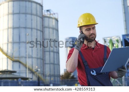 laborer outside a factory working dressed with safety overalls equipment - stock photo