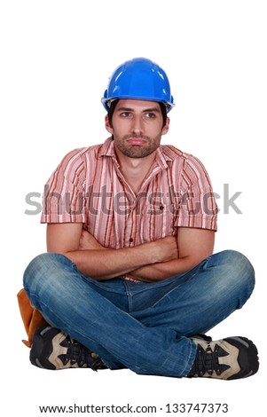 Laborer sitting with arms crossed - stock photo