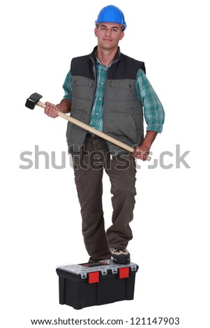 Laborer standing on his toolbox - stock photo