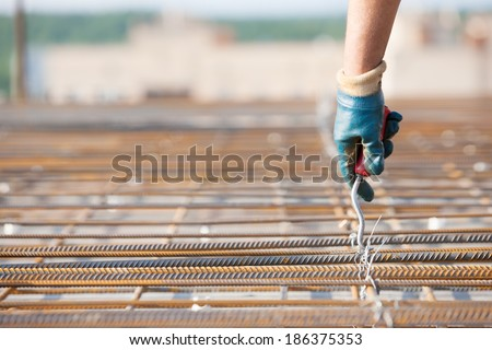Laborer worker installing binding wires to reinforcement steel bars at construction site during concrete pouring works with formwork. Close up - stock photo