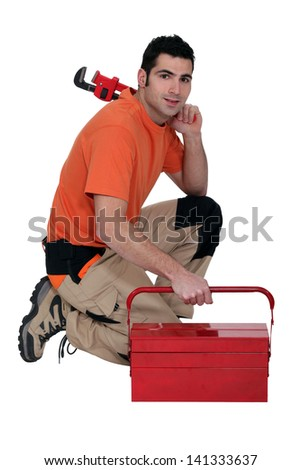 Labourer kneeling by tool box - stock photo